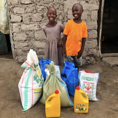 2 tanzanian children standing with bags of rices and other supplies