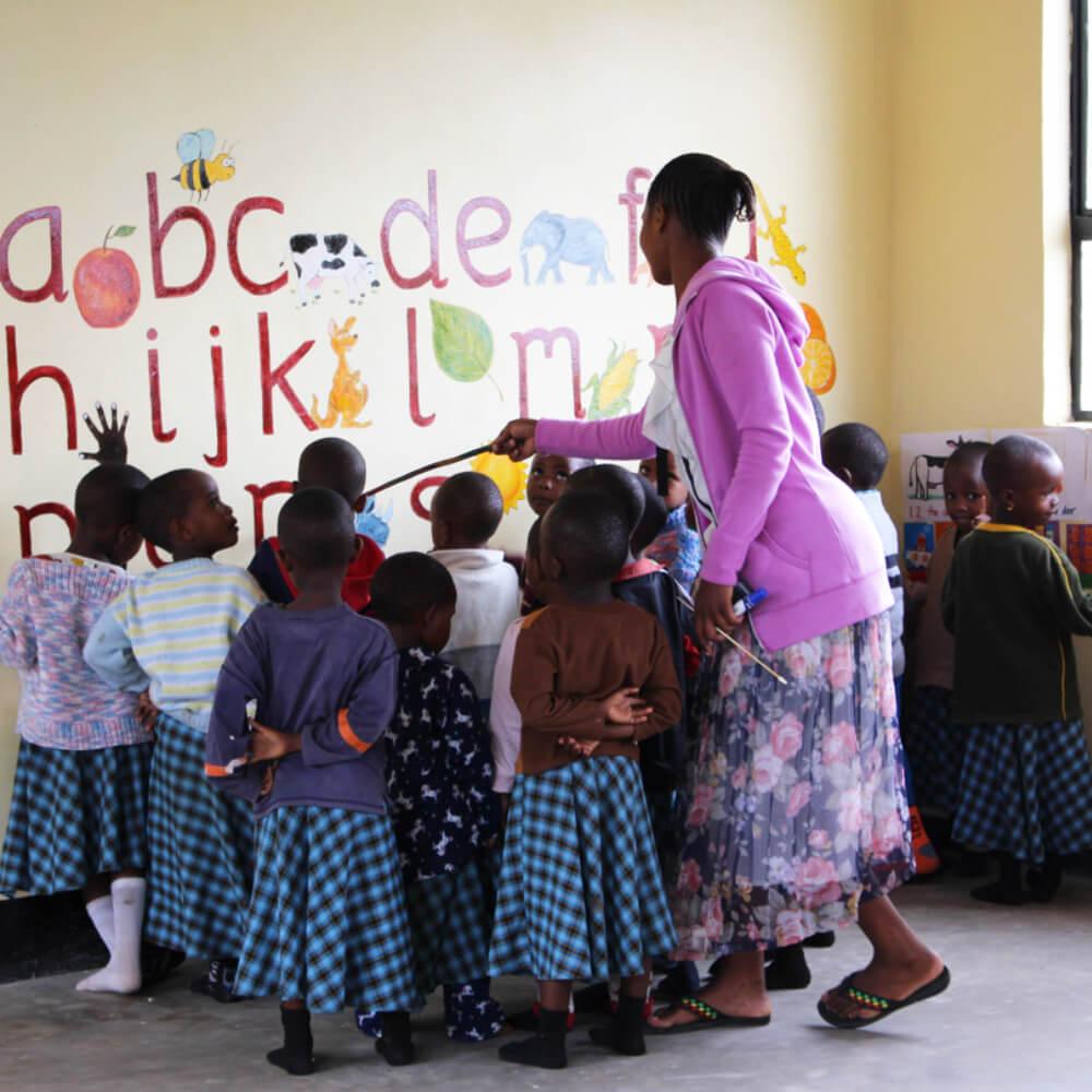 Teacher with class of Bandari students, teaching the alphabet