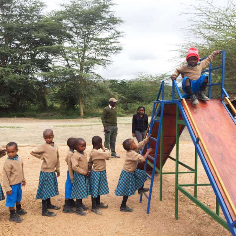 Bandari Project students waiting in line at Playground slide