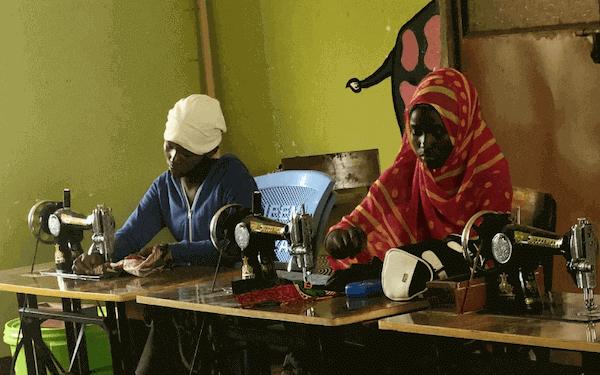 2 Tanzanian women sewing at treadle sewing machines