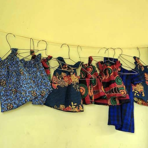 Brightly coloured children's dresses hanging on a line