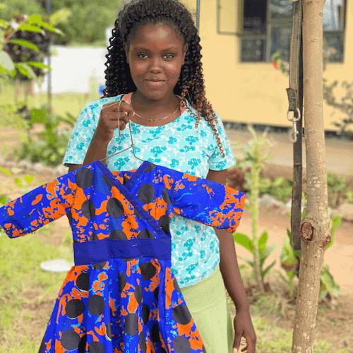 Smiling Tanzanian woman holding blue and orange dress