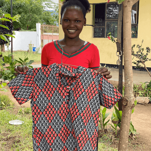 Smiling Tanzanian woman holding brightly coloured shirt
