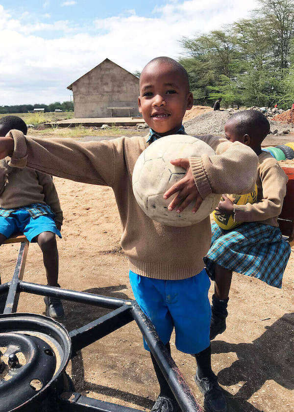 Bandari Project Student holding soccer ball in Playground