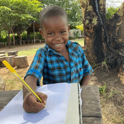 Bandari student sitting at table outside, writing in notebook