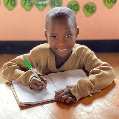 Bandari student sitting at table writing in notebook